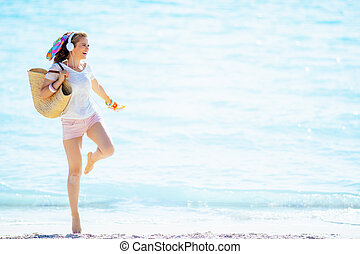 woman holding flip flops, listening to music with headphone