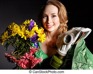 Woman holding flowers and gas mask . - Young woman holding...