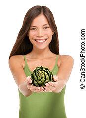 Woman holding fresh artichoke vegetable in hands