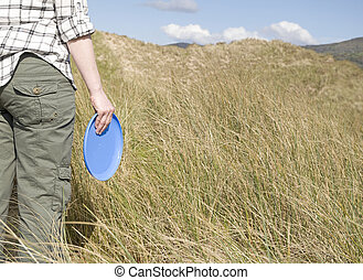 woman holding frisbee in sand dunes on sunny day