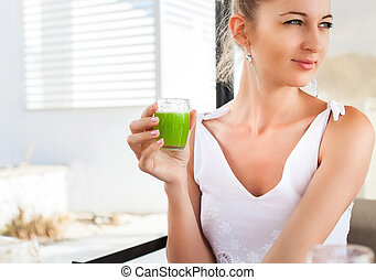 Woman holding glass of a green juice in her hand