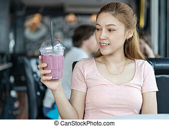 woman holding glass of blueberry smoothies in cafe