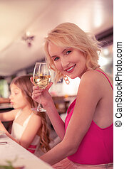 Woman holding glass of champagne while sitting near daughter