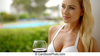 Woman Holding Glass of Red Wine Outdoors near Pool
