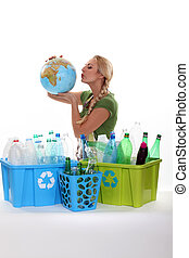 Woman holding globe recycling bottles