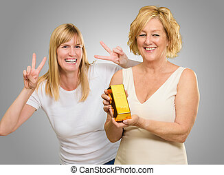 Woman Holding Gold Bar While Other Woman Gesturing Behind On...