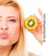 Woman holding green kiwi fruit