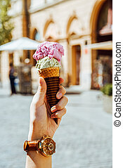 Woman Holding Green Pistachio And Pink Raspberry Ice Cream Cone In Hand