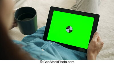 Woman Holding Greenscreen Tablet - Woman resting on couch, ...