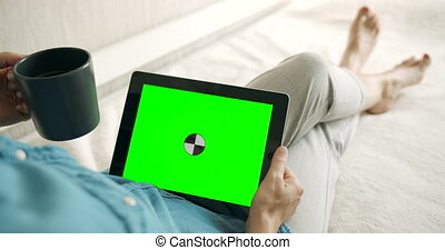 Woman Holding Greenscreen Tablet - Young female sitting on...