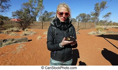 Happy tourist woman holding bark with pieces of Witchetty grilled food, which feed on the roots of witchetty bush of Northern Territory, Australia. Food of Aboriginal Australians diets. SLOW MOTION