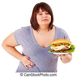 Woman holding hamburger. - Woman get abdomen pain after...