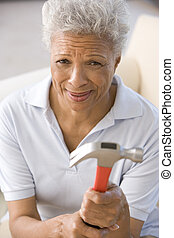 Woman holding hammer looking unsure