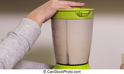 Woman holding hand near blender with protein cocktail