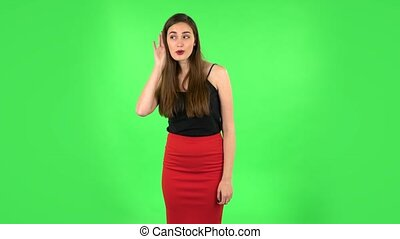 Woman holding hand near ear trying to listen to interesting news expressing communication concept and gossip. Brunette with long hair, a gentle makeup in black tank top and red skirt on green screen