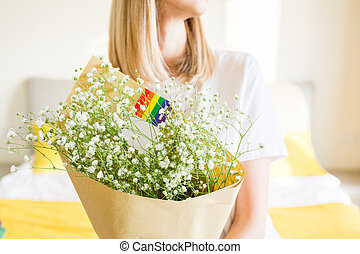 Woman holding hands bouquet of flowers with rainbow flag on bed. Lesbian celebrating pride month during Covid-19 Coronavirus pandemic quarantine, stay at home, social distancing and self isolation concept