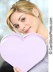 Woman holding heart-shaped box
