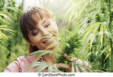 Woman holding hemp flowers - Young smiling woman in a hemp ...
