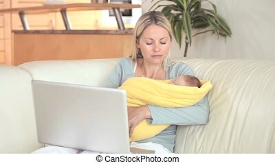 Woman holding her baby and using a laptop