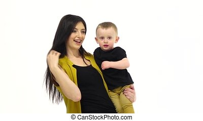 Woman holding her child in her arms. White background. Slow motion