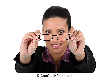Woman holding her glasses away from her face