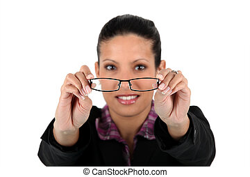 Woman holding her glasses in front of her face