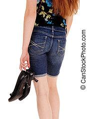 Woman holding her heels.