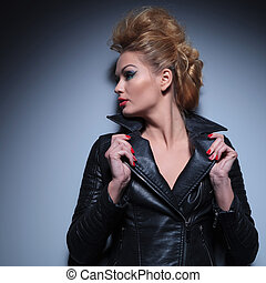 woman holding her leather jacket's collar and looks to her side away from the camera