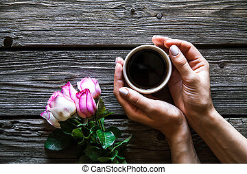 woman holding hot cup of coffee on a wooden background. Morning, drink, break
