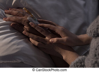 Woman holding ill mother hand