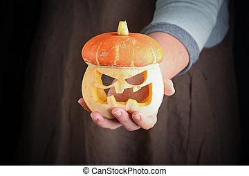Woman holding in hand freshly pumpkin, closeup. Carving A Pumpkin For Halloween.