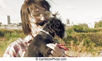 Woman holding in hands caressing little cute dog