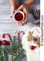 Woman holding in hands hot christmas tea with candy