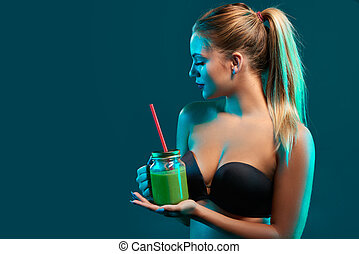 Woman holding jar mug with green smoothie drink