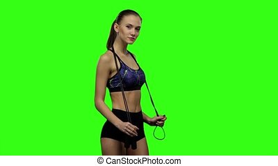 Woman holding jump rope on her shoulders. Slow motion. Green screen