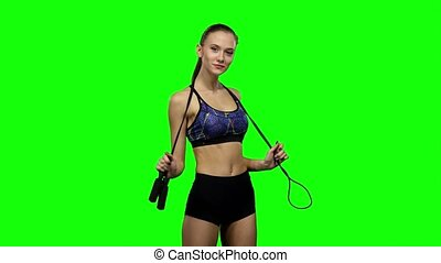 Woman holding jump rope on her shoulders. Green screen