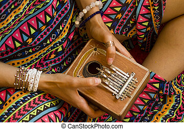 Woman holding kalimba in her hands and playing