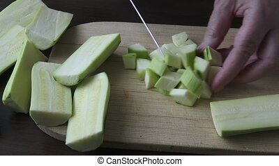 Woman holding kitchen knife, chopping peeled zucchini. Healthy eating concept.