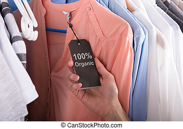 Woman Holding Label Showing 100 Percent Organic Cotton