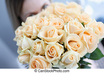 Woman holding large beautiful bouquet of white roses closeup