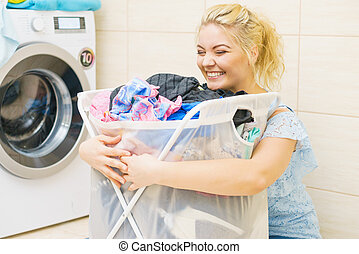 Woman holding laundry basket full of clothes