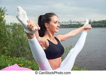 Woman holding legs apart doing exercises aerobics warming up
