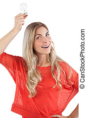 Woman holding light bulb above her head
