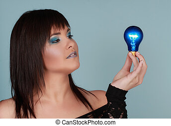 woman holding light bulb - young woman holding a blue...