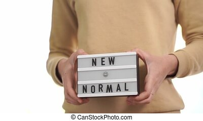 Woman holding lightbox with new normal text. post quarantine...