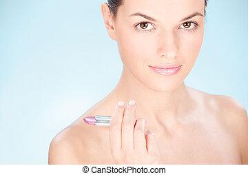 woman holding lipstick