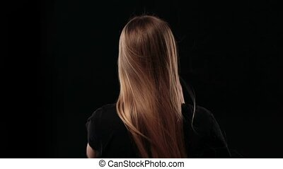 Back view of woman holding wonderful long hair and pulling her straight blond hair to show it's strength isolated on black background. Closeup rear view of blond female picking up hair in pony tail and demonstrating her strong healthy silky hair.