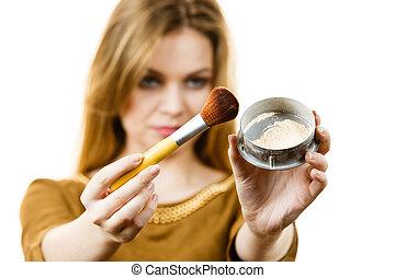 Woman holding make up brush