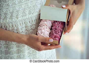 Woman holding marshmallows in a cardboard box