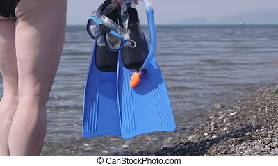 Woman holding mask and flippers going snorkeling in sea water